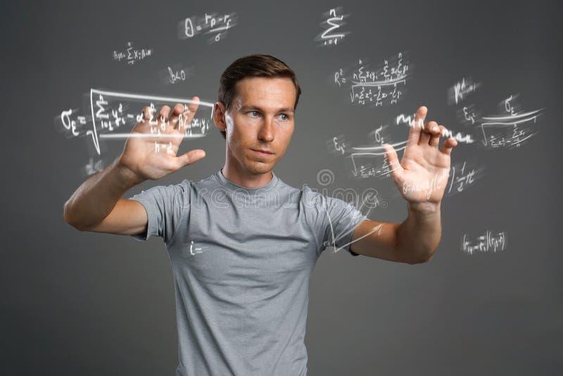 Obsługuje naukowa lub ucznia pracuje z różnorodnymi szkół średnich maths i nauk formułami obraz stock