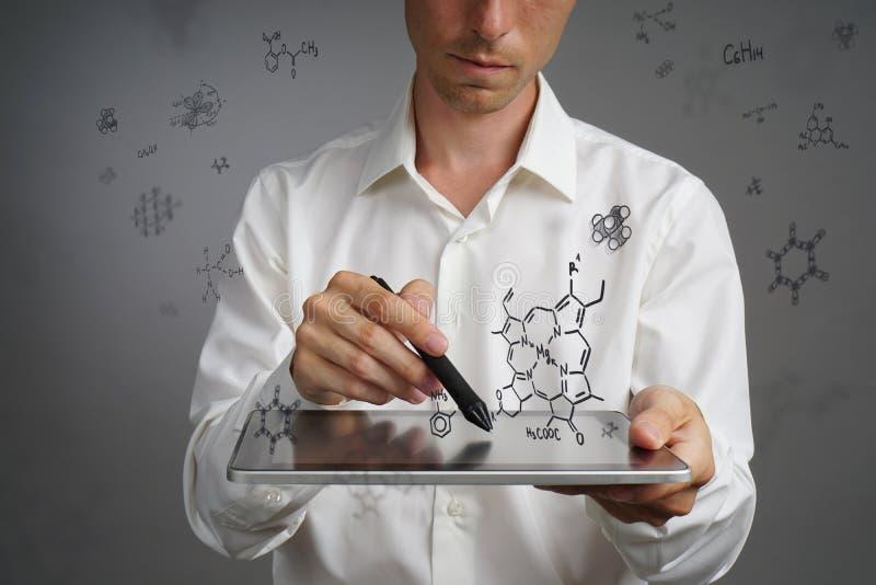 Obsługuje naukowa z, pisze działanie z chemicznymi formułami na szarym tle lub fotografia stock