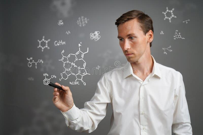Obsługuje naukowa z stylus lub pisze działanie z chemicznymi formułami na szarym tle obraz royalty free