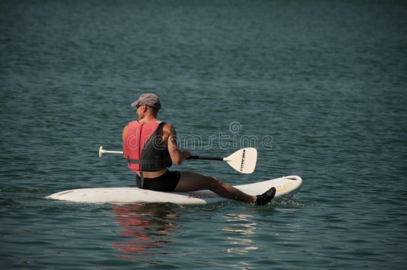 Obsługuje obsiadanie dalej stoi up paddle deskę z kamizelką ratunkową na jeziorze zdjęcia royalty free