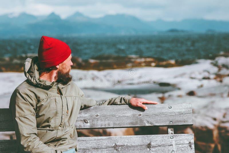 Obsługuje obsiadanie na ławce cieszy się morze i góry kształtują teren Podróżnego samotnego styl życia obraz royalty free