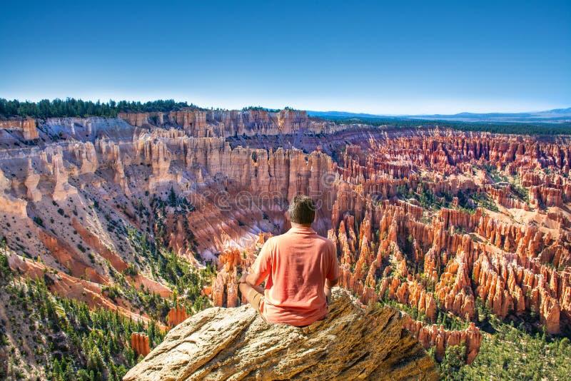 Obsługuje obsiadanie na górze góry patrzeje pięknego widok zdjęcie stock