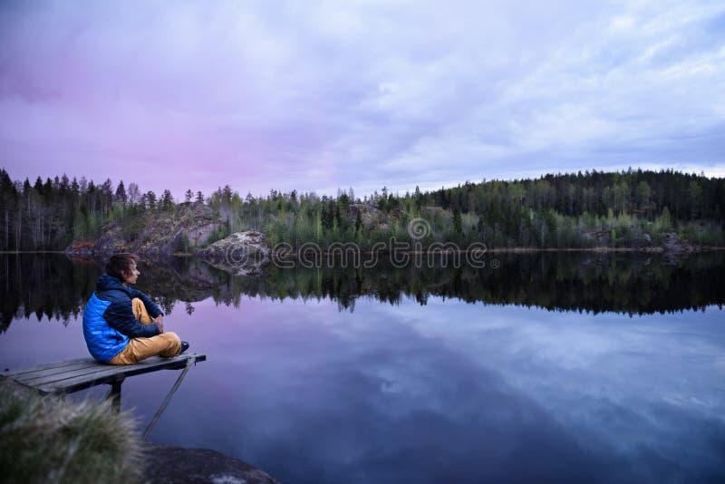 Obsługuje obsiadanie na molu przy halnym jeziorem, patrzeje widok fotografia stock