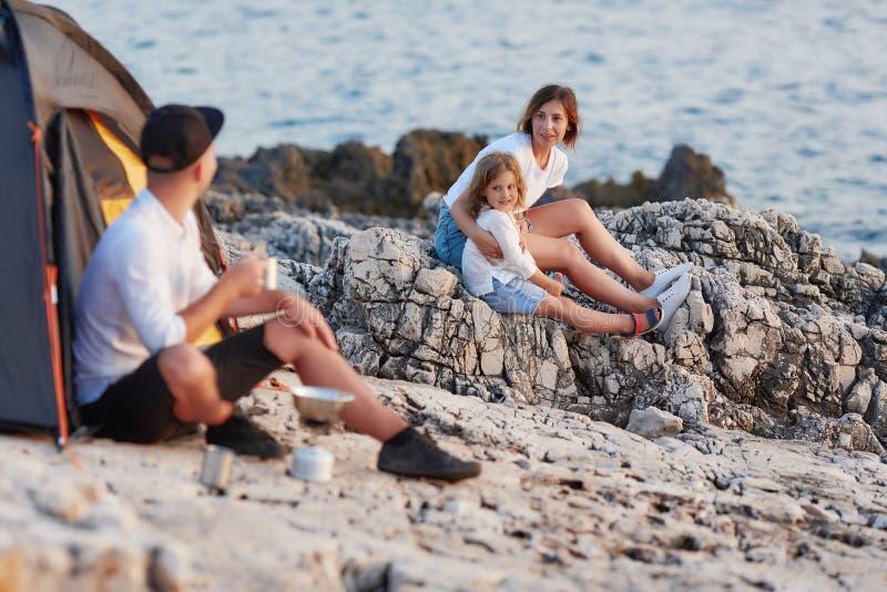 Obsługuje obsiadanie na skalisty brzegowym patrzejący żony siedzi blisko córki i, obraz stock