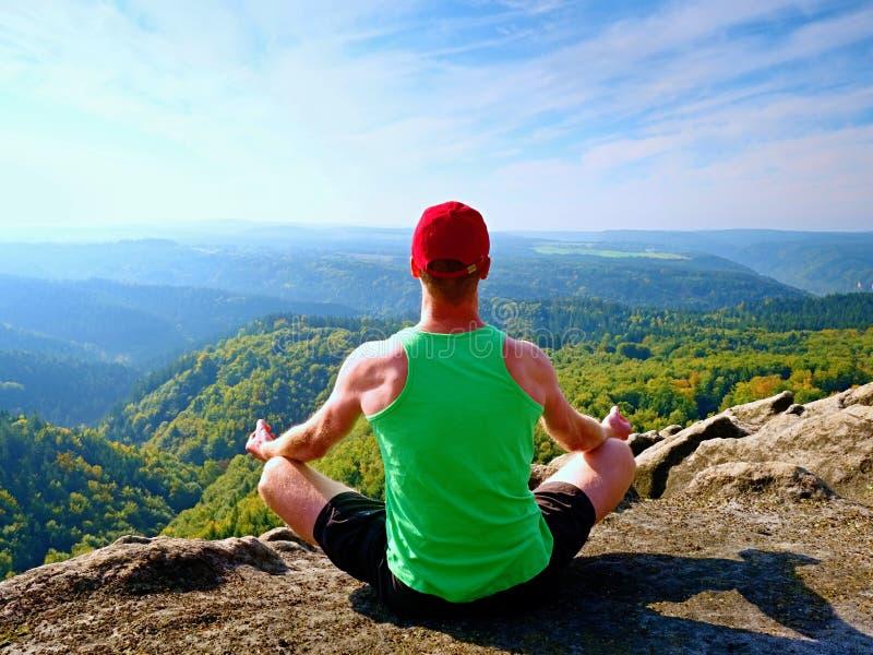 Obsługuje obsiadanie na wierzchołku góra w joga pozie Ćwiczy joga na krawędzi z breathtaking widokiem fotografia royalty free
