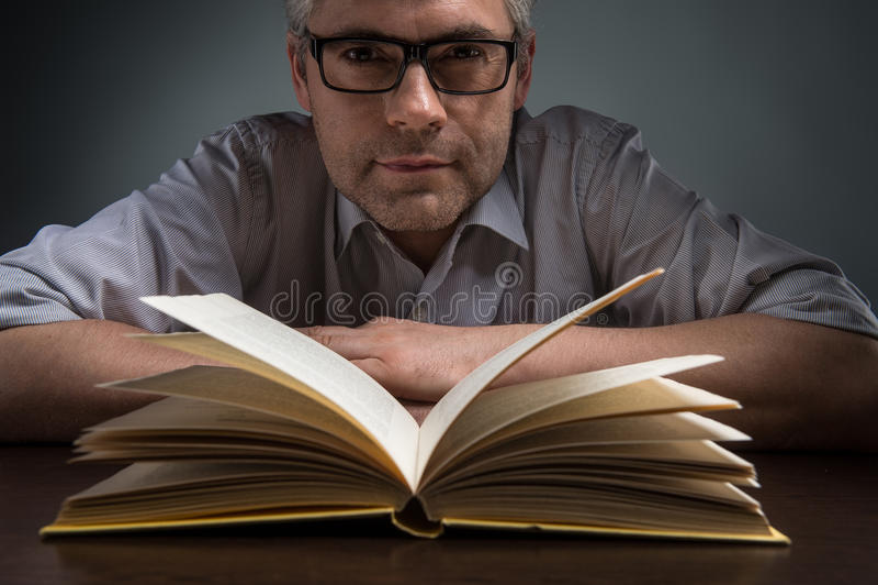 Obsługuje obsiadanie przy brąz stołową i czytelniczą książką obrazy stock
