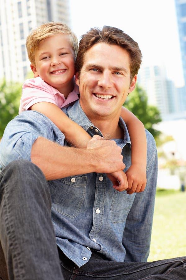 Obsługuje obsiadanie w miasta parku z młodym synem fotografia royalty free