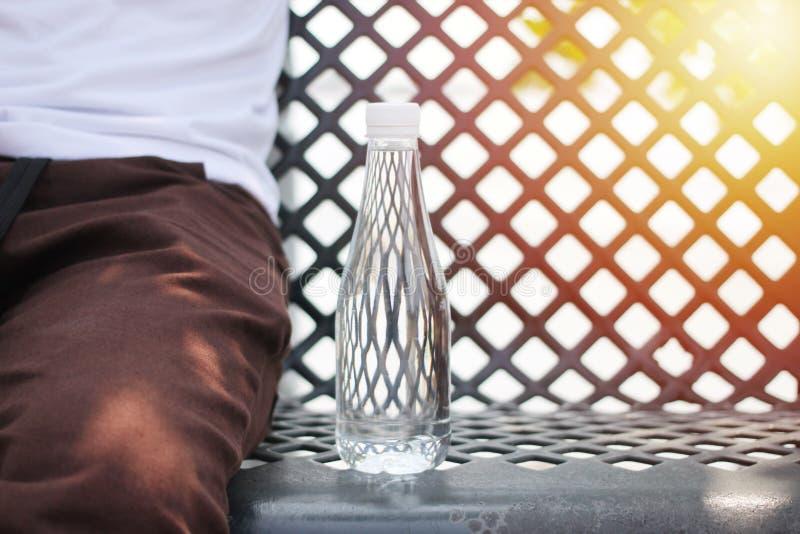 Obsługuje obsiadanie w ogródzie z butelką woda pitna zdjęcia stock
