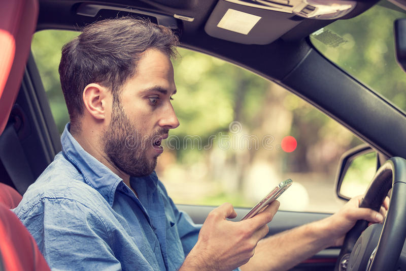 Obsługuje obsiadanie w samochodzie z telefonem komórkowym w ręce texting podczas gdy jadący zdjęcie royalty free