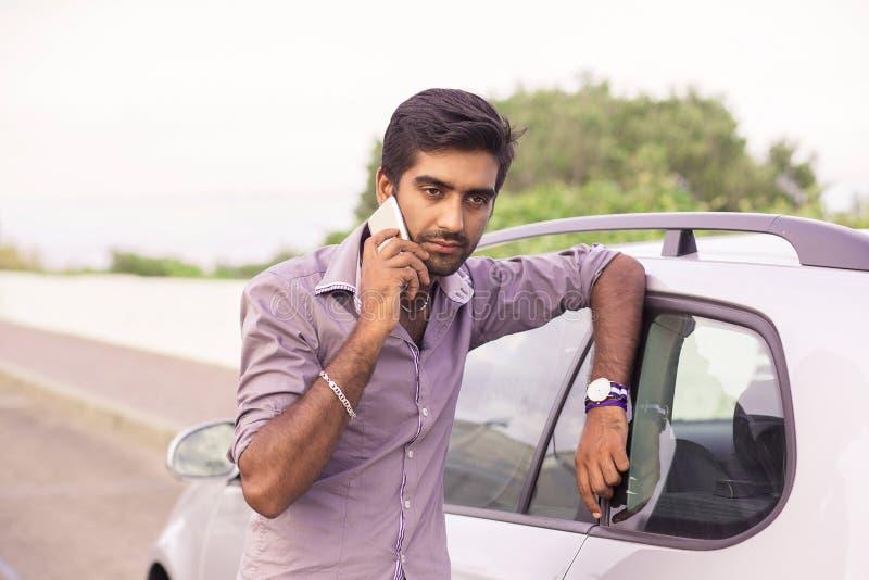 Obsługuje opowiadać na telefonie komórkowym opiera na drzwi jego samochód obrazy stock