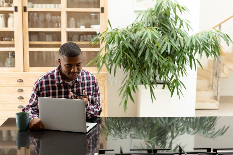 Obsługuje opowiadać na telefonie komórkowym podczas gdy używać laptop na worktop w kuchni fotografia stock
