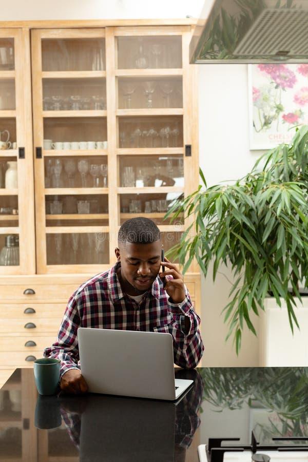Obsługuje opowiadać na telefonie komórkowym podczas gdy używać laptop na worktop w kuchni zdjęcia stock