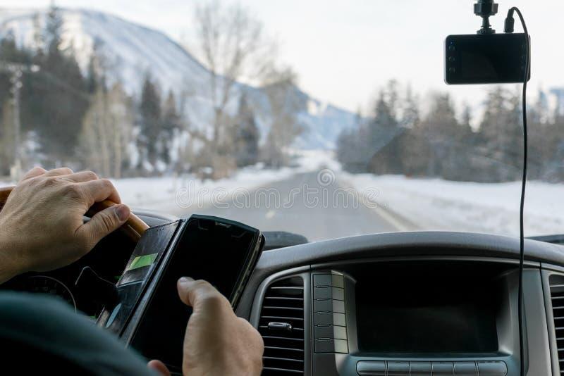 Obsługuje opowiadać na telefonie podczas gdy jechać samochód na śliskim śniegu zakrywał drogę zdjęcie stock