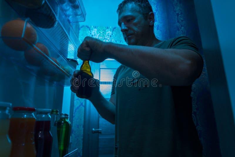 Obsługuje otwierać butelkę zimny piwo od fridge zdjęcie royalty free