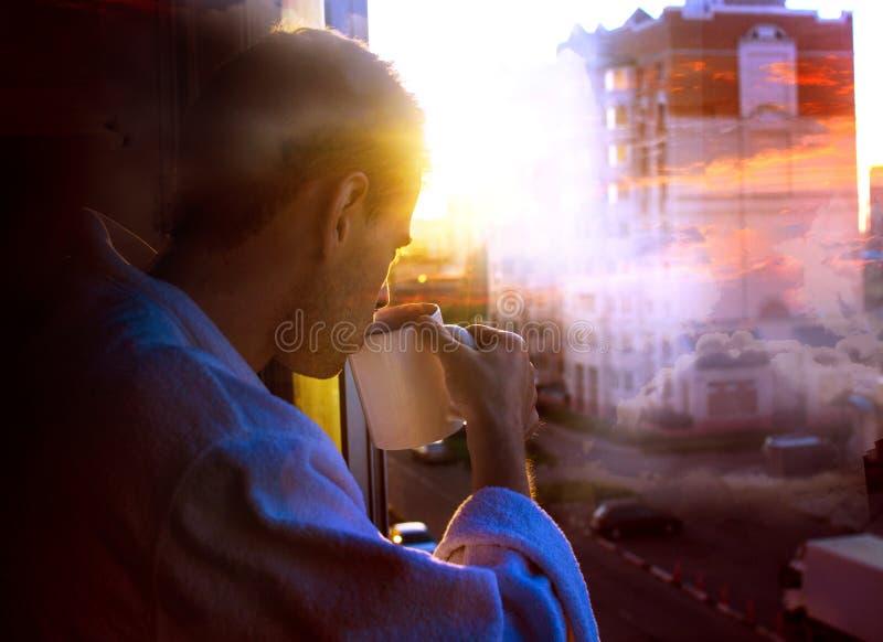 Obsługuje pić kawę od kubka przeciw tłu chmury, dwoisty ujawnienie fotografia stock