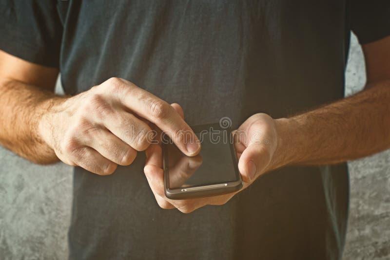 Obsługuje pisać na maszynie wiadomość tekstową na jego mądrze telefonie, selekcyjna ostrość zdjęcia royalty free