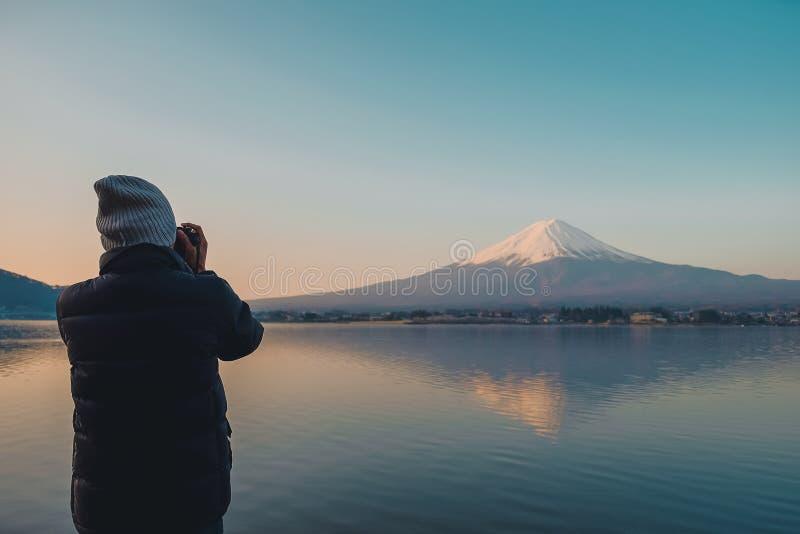 Obsługuje podróżnik pozycję i brać fotografii Piękną górę Fuji z śniegiem nakrywającym w ranku wschód słońca przy Jeziornym kawag fotografia stock