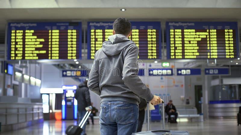 Obsługuje podróżnika patrzeje rozkład zajęć w dworcu, przygotowywa dla odjazdu zdjęcie royalty free