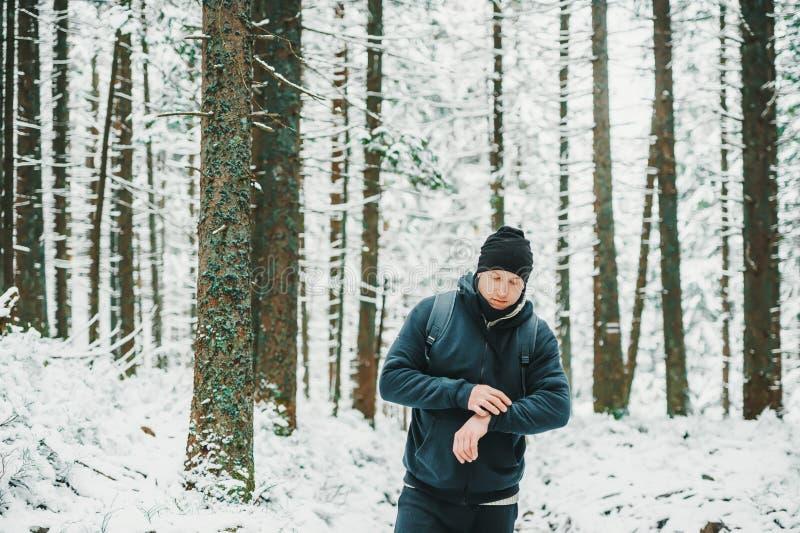 Obsługuje podróżnika w nakrętce, używa technologia sportów zegarek dla żeglować gps elektronicznego kompas w zima lesie, z plecak fotografia stock