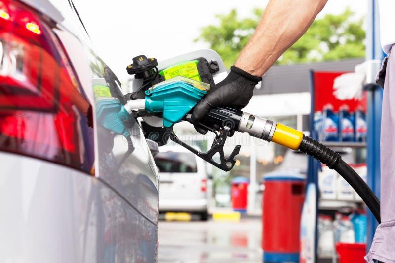 Obsługuje podsadzkowego olej napędowego w samochodzie przy benzynową stacją fotografia royalty free