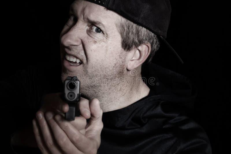 Obsługuje pokazywać złość z bronią wskazuje naprzód w zmroku zdjęcia royalty free
