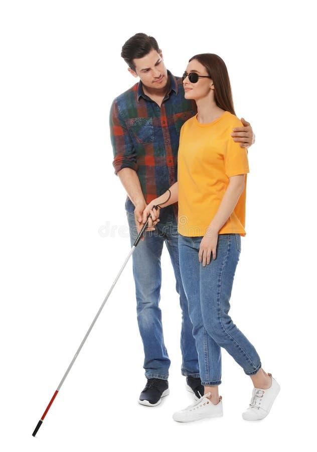 Obsługuje pomagać niewidomej kobiety z długą trzciną na bielu zdjęcia stock