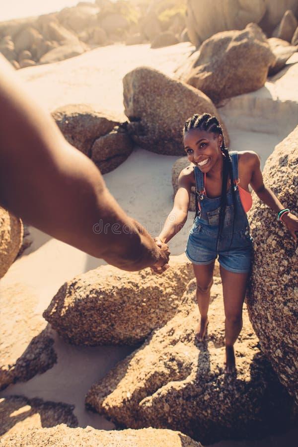 Obsługuje pomaga kobiety pięcia skałę przy plażą zdjęcia stock