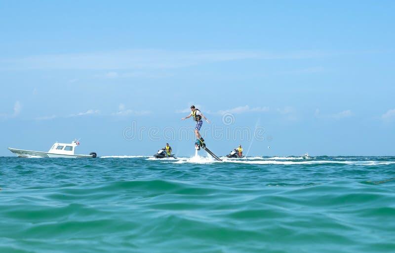 Obsługuje pozować przy nowym flyboard przy Karaibską tropikalną plażą Pozytywne ludzkie emocje, uczucia, radość Śmieszni śliczni  fotografia stock