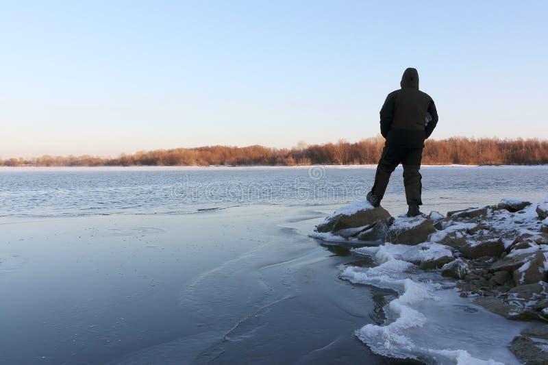 Obsługuje pozycję na kamieniach przy marznięcie rzeką przy zmierzchem zdjęcie royalty free