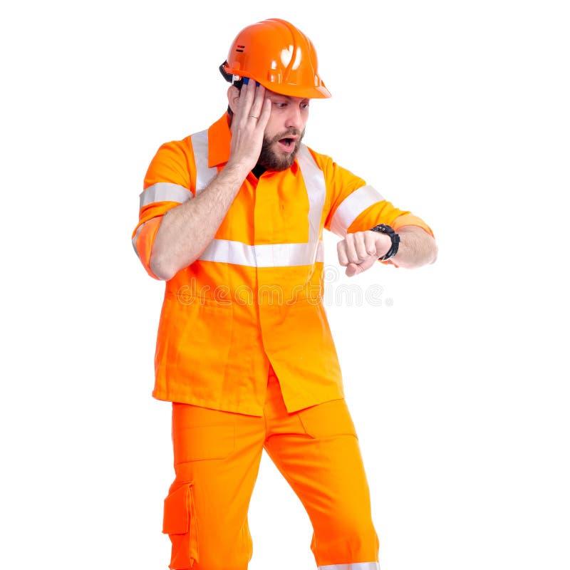 Obsługuje pracownika drogowego konstruktora patrzeje na zegarku, ostateczni terminy zdjęcia royalty free