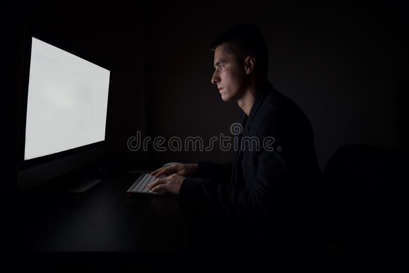 Obsługuje pracujący patrzeć i pisać na maszynie na komputerowej klawiaturze monitoru ekran podczas nocy - pracuje w biurze obrazy stock