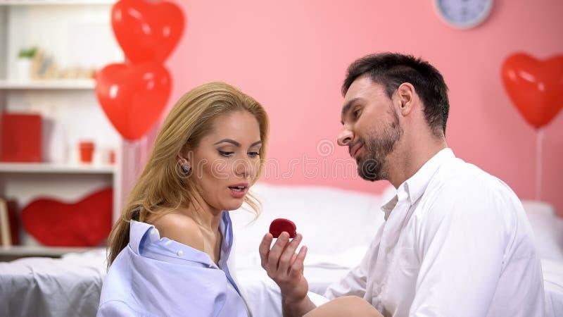 Obsługuje przedstawiać szokującego kobieta pierścionek zaręczynowego, dama patrzeje biżuterii teraźniejszość obraz royalty free