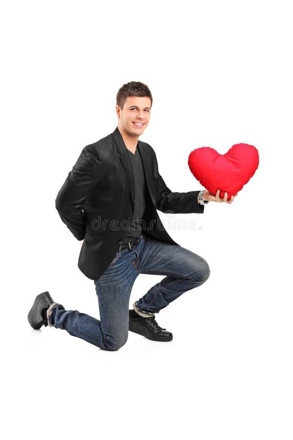 Obsługuje przycupnięcie na jeden mieniu i kolanie czerwony serce fotografia stock
