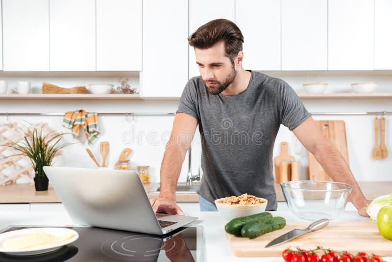 Obsługuje przyglądającego przepis na laptopie w kuchni w domu obraz stock