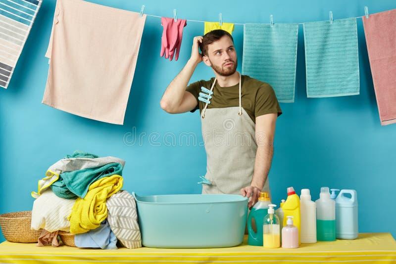 Obsługuje przyglądającego w górę, scaratching jego głowę, intrygujący podczas gdy myjący odziewa zdjęcia stock