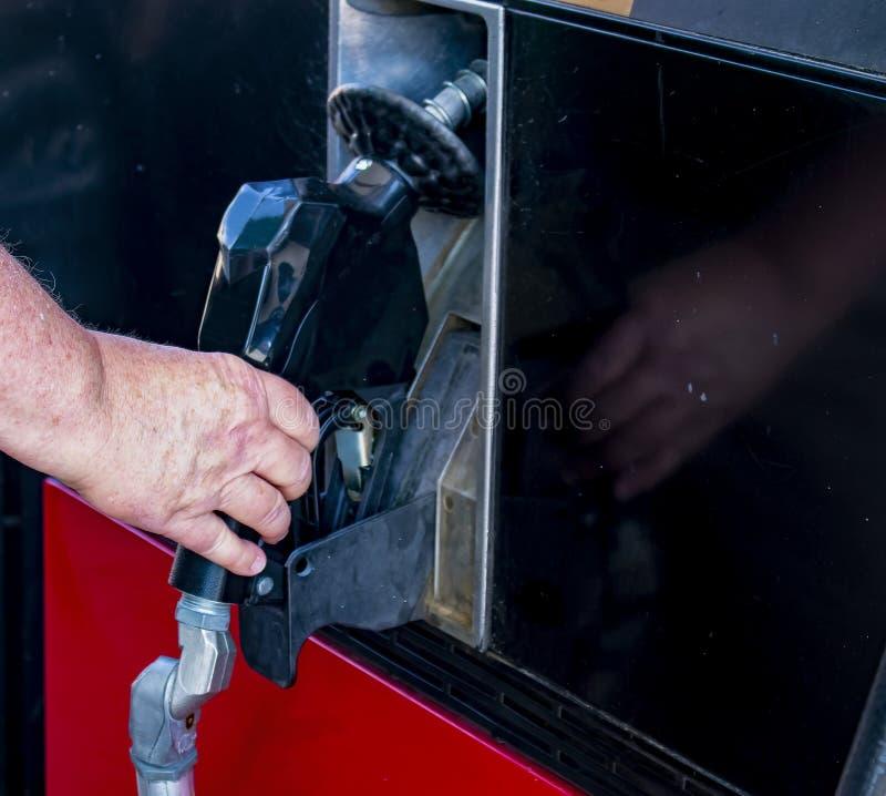 Obsługuje rękę chwyci nozzle benzynowa pompa usuwać je wypełniać up pojazd z gazem fotografia stock