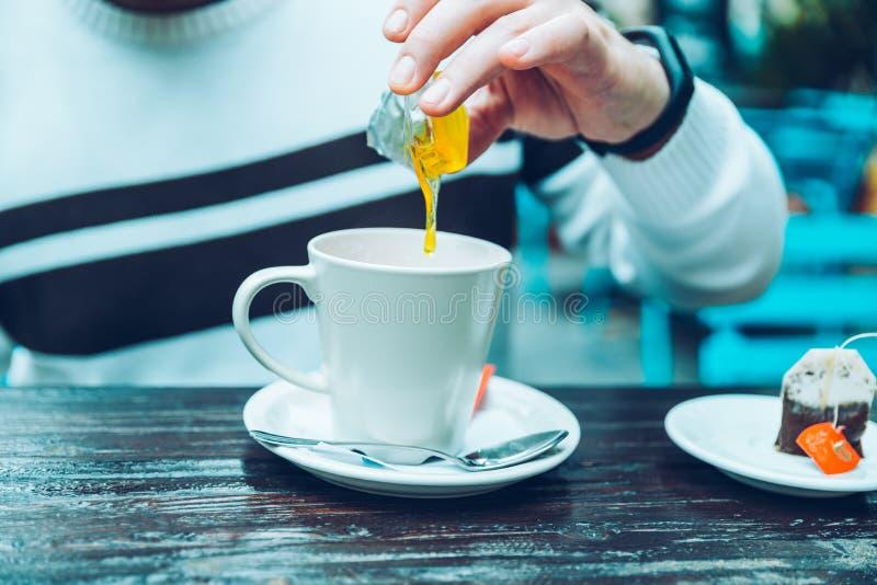 Obsługuje rękę dodaje miód jego herbata obraz royalty free