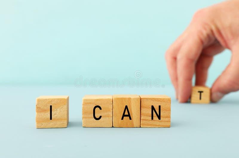 obsługuje rękę literuje słowo Ja CAN& x27; T od drewnianych sześcianów, bierze list T więc ja pisać MOGĘ sukcesu i wyzwania pojęc obrazy stock
