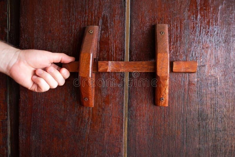 Obsługuje rękę na rękojeści drewnianym antycznym drzwi otwierać je lub zamykać obraz stock