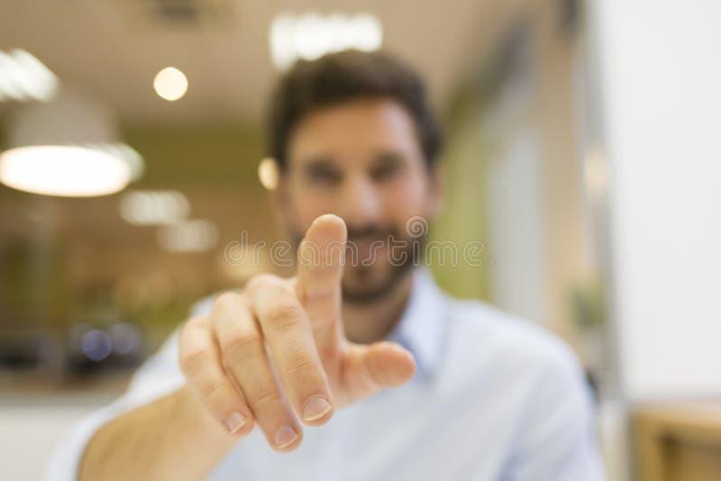 Obsługuje rękę pcha cyfrowego ekran na biurowym tle zdjęcie stock