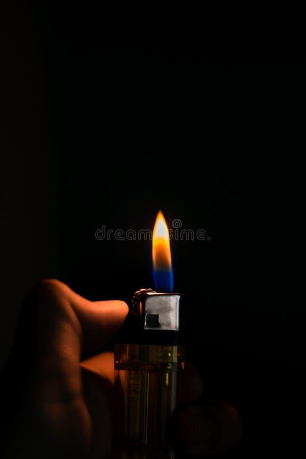 Obsługuje rękę trzyma papierosową zapalniczkę, czarny tło zdjęcia royalty free