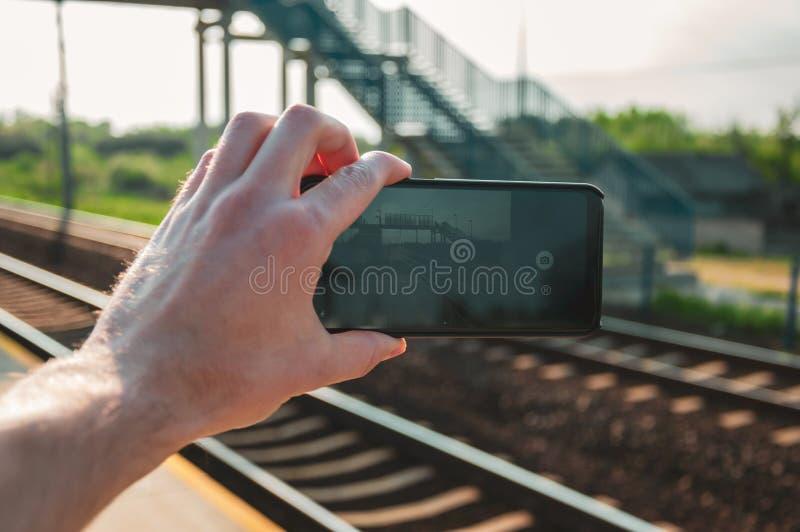 Obsługuje rękę trzyma smartphone i bierze fotografię stacja kolejowa podczas wiosny, południe zdjęcia stock