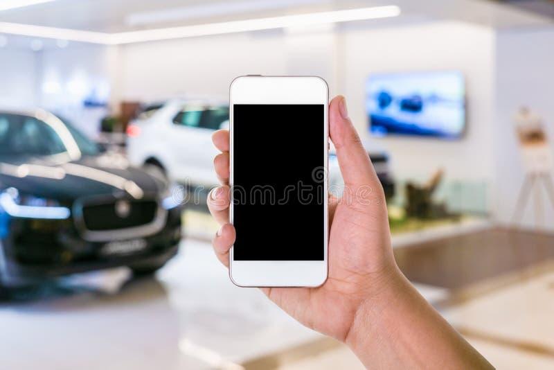 obsługuje rękę używać mobilnego mądrze telefon z pustym ekranem w zamazanym obraz royalty free