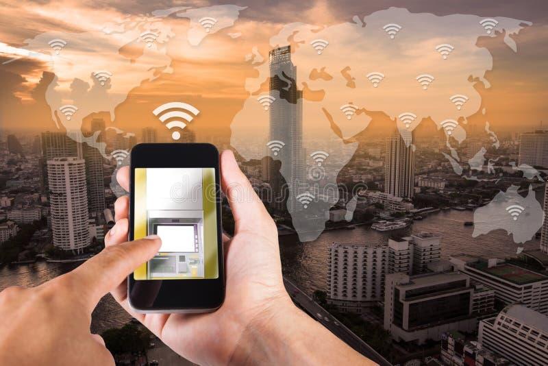 Obsługuje rękę używać smartphone mobilną bankowość na odgórnego widoku pejzażu miejskim obraz royalty free