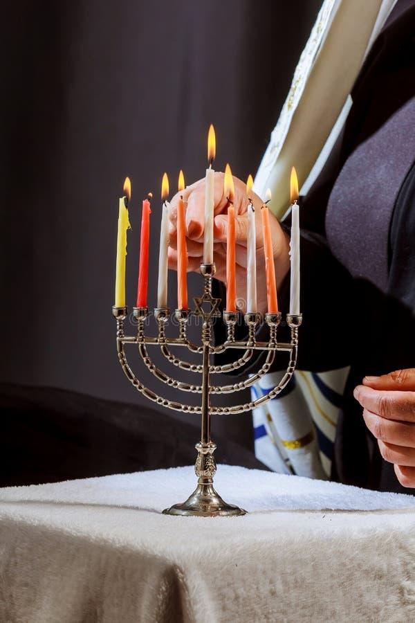 obsługuje ręk oświetleniowe świeczki w menorah na stole słuzyć dla hanukka zdjęcie stock