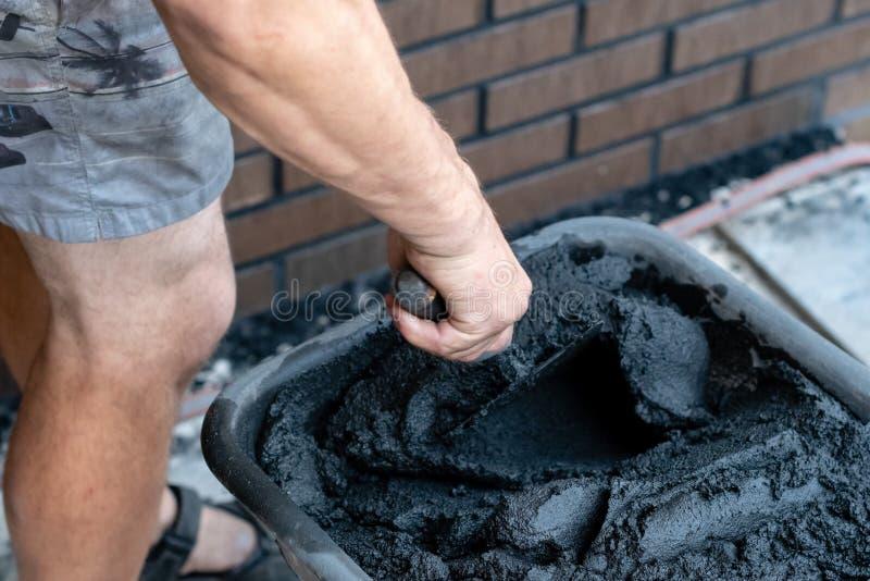 Obsługuje ręka chwyt mieszający cement w wiadrze i kielnia obrazy stock