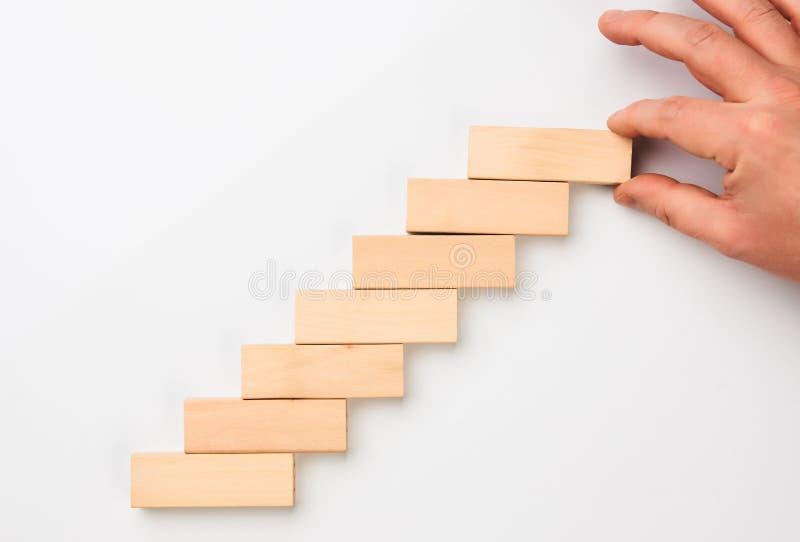 Obsługuje ręka stawiających drewnianych bloki w formie schody zdjęcie royalty free