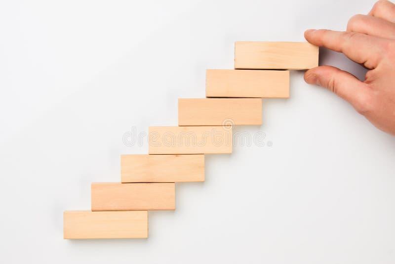 Obsługuje ręka stawiających drewnianych bloki w formie schody obraz royalty free