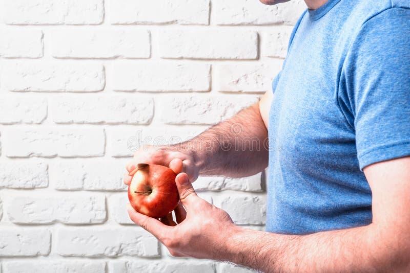 Obsługuje rżniętego jabłka w ręce na ceglanym tle zdjęcie stock