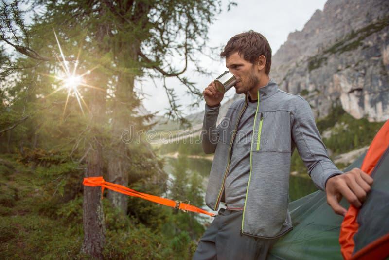Obsługuje relaksującego pobliskiego jeziornego wiszącego namiotowego camping pije gorącego napój Grupa przyjaciele zaludnia lato  obrazy royalty free